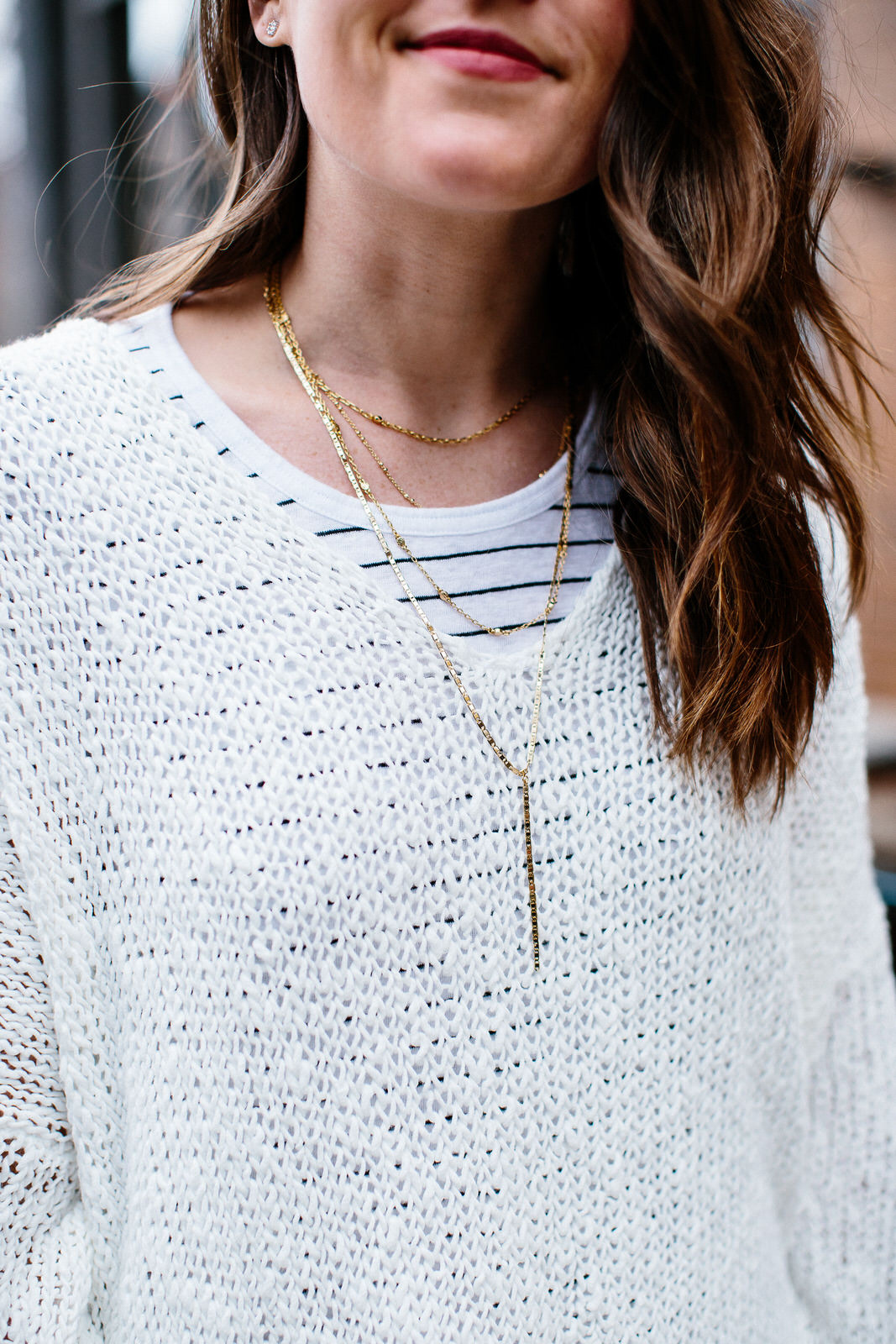 Easy ways to layer for spring wearing Free People sweater and stripe tee.