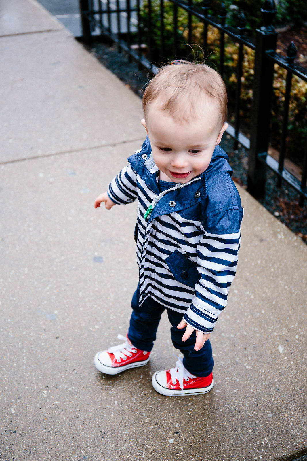 Baby boy wearing high top converse sneakers and stripe rain coat.